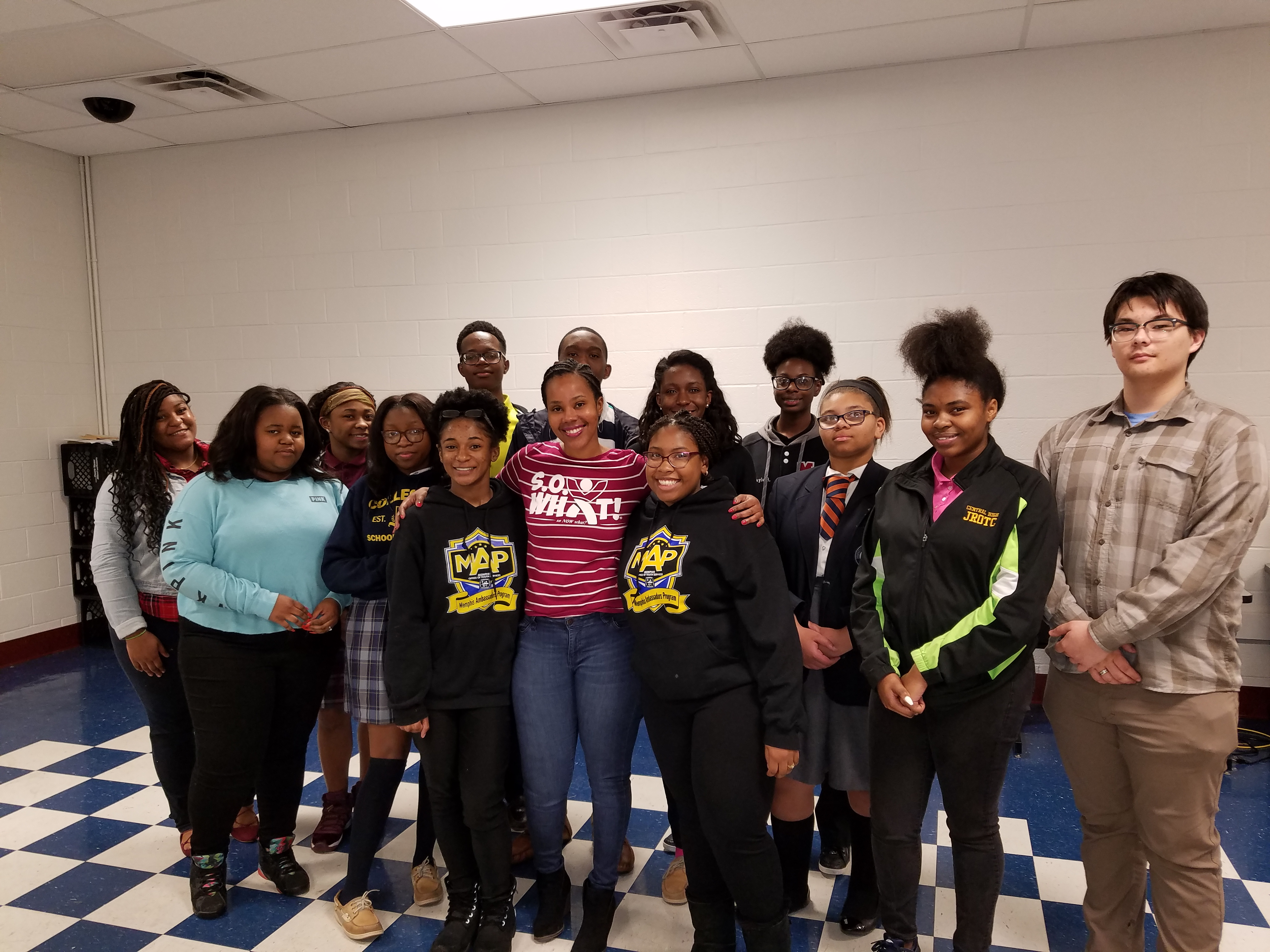 Summer Owens, motivational speaker poses with high school students who used the S.O. What! curriculum